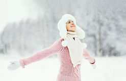 η ευτυχής χαμογελώντας γυναίκα που φορά ένα πουλόβερ και ένα καπέλο απολαμβάνει τη χειμερινή ημέρα Στοκ εικόνα με δικαίωμα ελεύθερης χρήσης