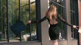 Η ευτυχής χαμογελώντας νέα γυναίκα εύθυμη στην ευδαιμονία απολαμβάνει τις επιτυχείς αγορές της απόθεμα βίντεο