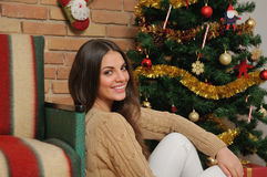 Η ευτυχής χαμογελώντας νέα γυναίκα με παρουσιάζει κοντά στο χριστουγεννιάτικο δέντρο στο χ Στοκ εικόνες με δικαίωμα ελεύθερης χρήσης