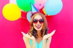 Η ευτυχής χαμογελώντας νέα γυναίκα πορτρέτου σε γενέθλια ΚΑΠ έχει τη διασκέδαση πέρα από ένα ζωηρόχρωμο ροζ μπαλονιών αέρα Στοκ φωτογραφία με δικαίωμα ελεύθερης χρήσης