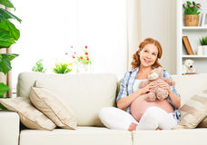 Η ευτυχής χαλάρωση εγκύων γυναικών στο σπίτι με το παιχνίδι teddy αντέχει Στοκ φωτογραφίες με δικαίωμα ελεύθερης χρήσης