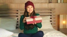 η ευτυχής όμορφη ασιατική κινεζική γυναίκα στη συνεδρίαση χειμερινών καπέλων στο χριστουγεννιάτικο δώρο εκμετάλλευσης κρεβατιών δ απόθεμα βίντεο
