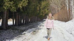 Η ευτυχής όμορφη γυναίκα περπατά στο χειμερινό δάσος μια ηλιόλουστη ημέρα κίνηση αργή φιλμ μικρού μήκους