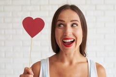 Η ευτυχής όμορφη γυναίκα που κρατά την κόκκινη καρδιά εγγράφου και φαίνεται αυτό Στοκ Εικόνα