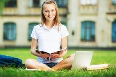 Η ευτυχής όμορφη γυναίκα σπουδαστών κάθεται στο χορτοτάπητα στα univers στοκ εικόνα