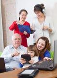 Η οικογένεια Ν χρησιμοποιεί λίγες διάφορες ηλεκτρονικές συσκευές Στοκ εικόνα με δικαίωμα ελεύθερης χρήσης