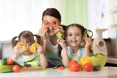 Η ευτυχή οικογενειακά μητέρα και τα παιδιά που έχουν τη διασκέδαση με τα λαχανικά τροφίμων στην κουζίνα κρατούν το πιπέρι μπροστά στοκ εικόνες