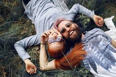 Η ευτυχία hipster συνδέει, στα γυαλιά ηλίου, την κοκκινομάλλη γυναίκα και το γενειοφόρο άνδρα, που κάθονται κάτω σε μια πράσινη χ στοκ εικόνες