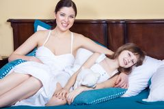 Η ευτυχία mom και το όμορφο κορίτσι της βρίσκονται στο κρεβάτι το πρωί, Στοκ Φωτογραφία