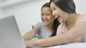 Η ευτυχείς ασιατικές οικογενειακές μητέρα και η κόρη χρησιμοποιούν το lap-top στο σπίτι απόθεμα βίντεο