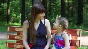 Η ευτυχείς μητέρα και η κόρη κάθονται στον πάγκο στο πάρκο στο καλοκαίρι φιλμ μικρού μήκους