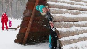 Η ευτυχείς μητέρα και η κόρη κοιτάζουν έξω από το ξύλινο σπίτι κατά τη διάρκεια των χιονοπτώσεων στο χειμερινό πάρκο απόθεμα βίντεο