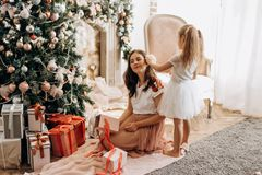 """Η ευτυχείς νέες μητέρα και λίγη κόρη στο συμπαθητικό φόρεμα κάθονται Ï"""" στοκ εικόνα"""