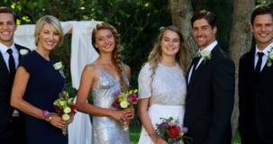 Η ευτυχείς νέοι νύφη και ο νεόνυμφος θέτουν με την οικογένεια και τους φίλους 4K 4k φιλμ μικρού μήκους