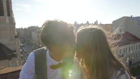 Η ευτυχείς νέοι όμορφοι μοντέρνοι νύφη και ο νεόνυμφος ζευγών φιλούν ήπια στη στέγη στην οδό πόλεων ηλιοβασιλέματος στο υπόβαθρο απόθεμα βίντεο