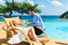 Η ευτυχείς νύφη και ο νεόνυμφος απολαμβάνουν ένα άπειρο poolside κοκτέιλ tropic στοκ φωτογραφία με δικαίωμα ελεύθερης χρήσης