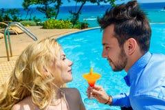 Η ευτυχείς νύφη και ο νεόνυμφος απολαμβάνουν ένα άπειρο poolside κοκτέιλ tropic στοκ φωτογραφίες