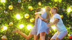 Η ευτυχείς οικογένεια, ο μπαμπάς, mom και η κόρη συναντούν το νέο έτος στο υπόβαθρο του χριστουγεννιάτικου δέντρου σε μια τροπική φιλμ μικρού μήκους