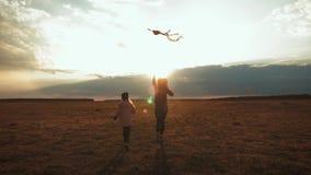 Η ευτυχείς οικογενειακή μητέρα και η κόρη παιδιών προωθούν έναν ικτίνο στο λιβάδι στο ηλιοβασίλεμα Αστείος οικογενειακός χρόνος Έ φιλμ μικρού μήκους