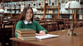 Η ευφυής γυναίκα διαβάζει στη βιβλιοθήκη απόθεμα βίντεο