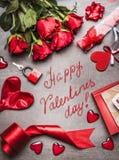 Η ευχετήρια κάρτα ημέρας βαλεντίνων με τα σύμβολα αγάπης, η κόκκινη διακόσμηση και τα όμορφα τριαντάφυλλα συσσωρεύουν, και ο χειρ στοκ εικόνες