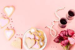 Η ευχετήρια κάρτα ημέρας του ευτυχούς βαλεντίνου με τα μπισκότα καρδιών, τα γυαλιά κρασιού και το κρασί στην κρητιδογραφία οδοντώ στοκ εικόνα με δικαίωμα ελεύθερης χρήσης