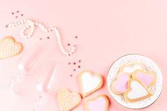Η ευχετήρια κάρτα ημέρας του ευτυχούς βαλεντίνου με τα μπισκότα καρδιών, τα γυαλιά κρασιού και το κρασί στην κρητιδογραφία οδοντώ στοκ φωτογραφίες