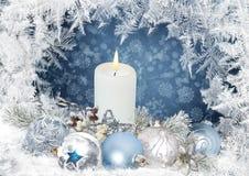 Η ευχετήρια κάρτα Χριστουγέννων με τα κεριά, πεύκο διακλαδίζεται, σφαίρες σε ένα μπλε υπόβαθρο με ένα παγωμένο σχέδιο Στοκ φωτογραφία με δικαίωμα ελεύθερης χρήσης