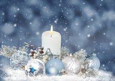 Η ευχετήρια κάρτα Χριστουγέννων με τα κεριά, πεύκο διακλαδίζεται, σφαίρες σε ένα μπλε υπόβαθρο Στοκ Εικόνα