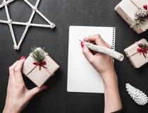 Η ευχετήρια κάρτα Χριστουγέννων, μια κυρία γράφει τον κατάλογο δώρων που θα παραθέσει Το περιβάλλον Χριστουγέννων συμπληρώνεται α Στοκ εικόνα με δικαίωμα ελεύθερης χρήσης