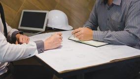 Η εφαρμοσμένη μηχανική ή ο αρχιτέκτονας κατασκευής συζητά ένα σχεδιάγραμμα ελέγχοντας τις πληροφορίες για το σχεδιασμό και τη σκι στοκ εικόνες