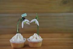 Η εύγευστη βανίλια cupcakes που ολοκληρώνεται με το φρέσκο snowdrop ανθίζει και ένα μικροσκοπικό ειδώλιο προσώπων με το σημάδι άν Στοκ Φωτογραφία