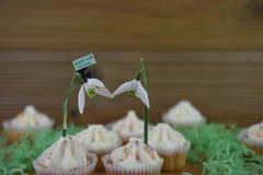 Η εύγευστη βανίλια cupcakes που ολοκληρώνεται με το φρέσκο snowdrop ανθίζει και ένα μικροσκοπικό ειδώλιο προσώπων με το σημάδι άν Στοκ εικόνα με δικαίωμα ελεύθερης χρήσης