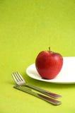 Η εύγευστη Apple στο άσπρο πιάτο στο πράσινο υπόβαθρο Στοκ Εικόνα