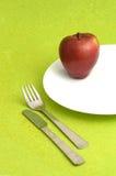 Η εύγευστη Apple στο άσπρο πιάτο στο πράσινο υπόβαθρο Στοκ φωτογραφίες με δικαίωμα ελεύθερης χρήσης