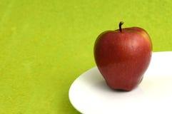 Η εύγευστη Apple στο άσπρο πιάτο στο πράσινο υπόβαθρο Στοκ Φωτογραφίες