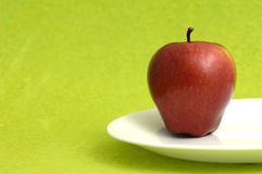 Η εύγευστη Apple στο άσπρο πιάτο στο πράσινο υπόβαθρο Στοκ Εικόνες