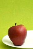Η εύγευστη Apple στο άσπρο πιάτο στο πράσινο υπόβαθρο Στοκ φωτογραφία με δικαίωμα ελεύθερης χρήσης