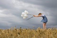 Η εύθραυστη γυναίκα κρατά τα μπαλόνια ενάντια στο ισχυρό άνεμο Στοκ Φωτογραφία