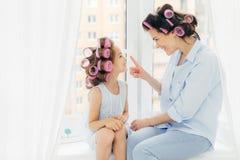 Η εύθυμες μητέρα δύο και daughter do hair ND έχουν τη διασκέδαση μαζί, έχουν τα ρόλερ στο κεφάλι, κάθονται στη στρωματοειδή φλέβα στοκ εικόνα