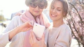 Η εύθυμες μητέρα και η κόρη προσέχουν τις φωτογραφίες στο smartphone Οι γυναίκες γελούν και συζητούν τις εντυπώσεις τους o απόθεμα βίντεο