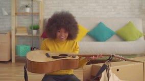 Η εύθυμη αφρικανική γυναίκα πορτρέτου με ένα afro hairstyle ανοίγει ένα νέο αργό MO κιθάρων απόθεμα βίντεο