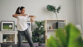 Η εύθυμη γυναίκα αφροαμερικάνων πηδά το χορό στον καναπέ ακούοντας στο σπίτι τη μουσική με τα ακουστικά απολαμβάνοντας το ρυθμό απόθεμα βίντεο