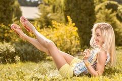 Η εύθυμη γυναίκα ομορφιάς χαλαρώνει, κήπος, άνθρωποι υπαίθριοι Στοκ Φωτογραφία