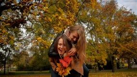 Η εύθυμη ευτυχής γυναίκα Piggybacking η όμορφη φίλη της, δύο όμορφα νέα κορίτσια που γελούν το φθινόπωρο σταθμεύει και απόθεμα βίντεο