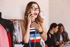Η εύθυμη νέα γυναίκα ντύνει το σχεδιαστή στο ατελιέ στοκ φωτογραφία με δικαίωμα ελεύθερης χρήσης
