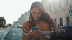 Η εύθυμη νέα γυναίκα που φορά το φόρεμα χρησιμοποιώντας το τηλέφωνό της στην ηλιόλουστη οδό πόλεων και πίνοντας παίρνει μαζί τον  απόθεμα βίντεο