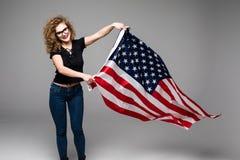 Η εύθυμη νέα γυναίκα στα περιστασιακά ενδύματα είναι κύμα η αμερικανική σημαία και χαμόγελο στο γκρίζο υπόβαθρο Στοκ εικόνα με δικαίωμα ελεύθερης χρήσης