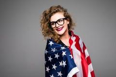 Η εύθυμη νέα γυναίκα στα περιστασιακά ενδύματα και τα γυαλιά καλύπτεται στη αμερικανική σημαία και χαμόγελο στο γκρίζο υπόβαθρο Στοκ εικόνα με δικαίωμα ελεύθερης χρήσης