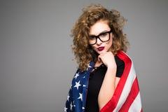 Η εύθυμη νέα γυναίκα στα περιστασιακά ενδύματα και τα γυαλιά καλύπτεται στη αμερικανική σημαία και χαμόγελο στο γκρίζο υπόβαθρο Στοκ Φωτογραφίες